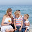 Attentive mother holding sunscreen at the beach — Stock Photo #10292227