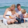 Stock Photo: Smiling mother with her family holding sunscreen