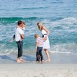 Happy family walking on the sand - Stock Photo