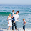 Affectionate family having fun at the beach - Stock Photo