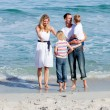 Happy family having fun on the sand — Stock Photo