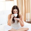 Pretty woman drinking coffee sitting on bed — Stock Photo #10292259