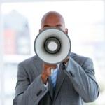 Ethnic businessman yelling through a megaphone — Stock Photo