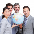 Confident businessteam looking at a terrestrial globe — Stock Photo