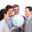 Foto Stock: Positive businessteam looking at terrestrial globe