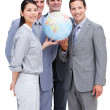 Foto Stock: Successful businessteam looking at terrestrial globe