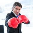 Furious businessman wearing boxing gloves — Stock Photo