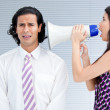 Angry businesswoman yelling through a megaphone - Stock Photo