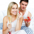 Couple celebrating an engagement with strawberries and champagne — Stock Photo