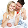 Young lovers eating strawberries and drinking champagne — Stock Photo