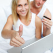 Couple in bed buying on-line successfully — Stock Photo