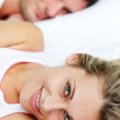 Beautiful smiling woman lying in bed with her boyfriend — Stock Photo #10292786
