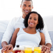 Afro-american couple having breakfast lying on their bed — Stock Photo