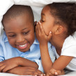 Ethnic little girl whispering something to her brother — Stock Photo #10292863