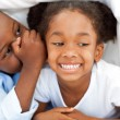 Ethnic little boy whispering something to his sister - Stock Photo