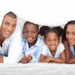 Merry family having fun lying down on bed — Stock Photo #10292878