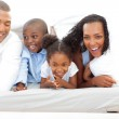 Lively family having fun lying down on bed — Stock Photo