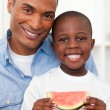 Portrait of a smiling boy eating fruit with his father — Stock Photo #10292973