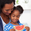 Beautiful girl eating watermelon with her mother — Stock Photo #10292983