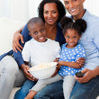 Royalty-Free Stock Photo: Portrait of a family eating popcorn and watching TV