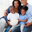 Portrait of a family eating popcorn and watching TV — Stock Photo