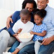 Stock Photo: Happy family eating popcorn and watching TV