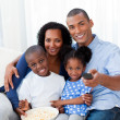 Smiling Afro-american family eating popcorn and watching TV — Stock Photo