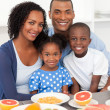 Happy family having healthy breakfast — Stockfoto
