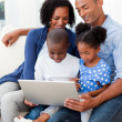 Happy family using a laptop — Stock Photo