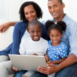 Smiling Afro-american family using a laptop — Stock Photo