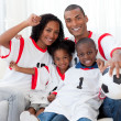 Afro-American family celebrating a football goal - Stock Photo