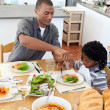 Ethnic little boy dining with his father — Stock Photo