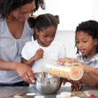 Ethnic family making biscuits together - Stock Photo