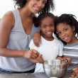 Stock Photo: Cute siblings with their mother making biscuits