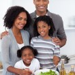 Ethnic family preparing salad together — Stock Photo