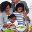 Affectionate family preparing salad together — Stock Photo