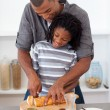 Stock Photo: Happy father slicing bread with his son
