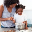 Stock Photo: Adorable little girl preparing biscuits with her mother