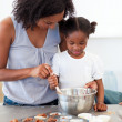 Adorable little girl preparing biscuits with her mother - Stock Photo