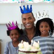 Royalty-Free Stock Photo: Joyful Afro-american father with his children celebrating a birt