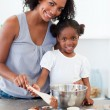 Attentive mother helping her girl cooking biscuits — Stock Photo