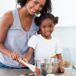 Stock Photo: Attentive mother helping her girl cooking biscuits