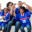 图库照片: Excited Afro-American family watching a football match