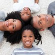Smiling Afro-American young family lying on floor — Stock Photo