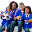 Afro-American family watching a football match at home — Stok fotoğraf