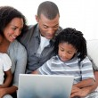 Afro-American family using a laptop on the sofa — Stock Photo