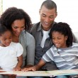 Afro-American family reading a book in the living-room — Stock Photo