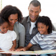Afro-American family reading a book in the living-room — Stock Photo #10293263