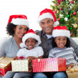 Afro-American family holding Christmas presents — ストック写真