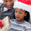 Portrait of an Afro-American father and son opening a Christmas — Stok fotoğraf